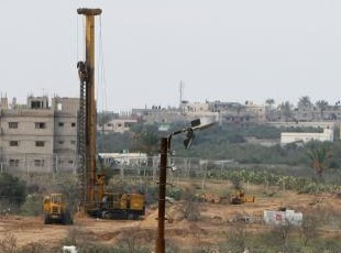 Photographed by: AFP Machinery on the Egyptian side of borders area work in building the separating area between...